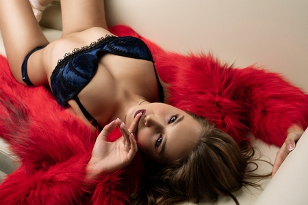 Gorgeous girl in red fur coat lying on a sofa view