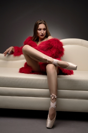 Gorgeous girl in red fur coat reclining in a sofa