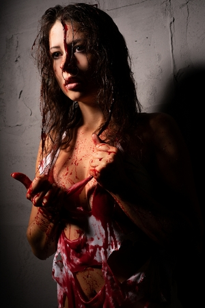 Sexy girl splashed with blood against gray wall