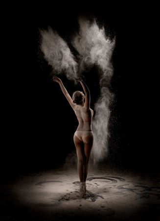 Blonde topless dancing in white powder cloud rearview