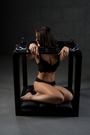 Handcuffed brunette in black lingerie in the dark
