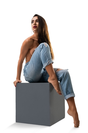 Girl topless sitting on a cube isolated shot Stock Photo