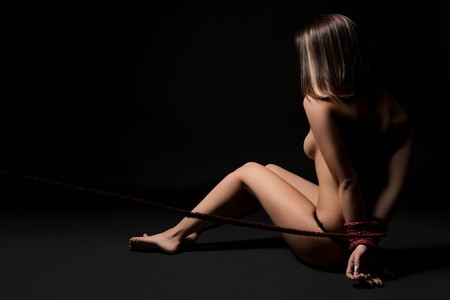 Nude girl tied up in shibari art style rearview