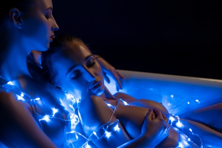 Two nude girls in the bath in blue garland lights