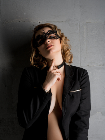 Pretty blonde in lace mask and jacket shot Foto de archivo