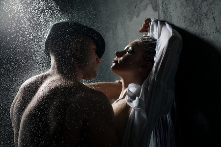 Young couple embracing in shower in the dark 版權商用圖片