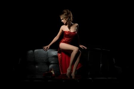 Chica sexy en vestido rojo relajante en el sofá Foto de archivo