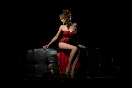 Fille sexy en robe rouge relaxante sur le canapé Banque d'images