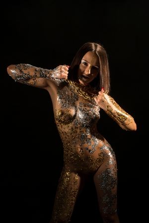 Naked girl with gold bodyart and chain on her neck Фото со стока