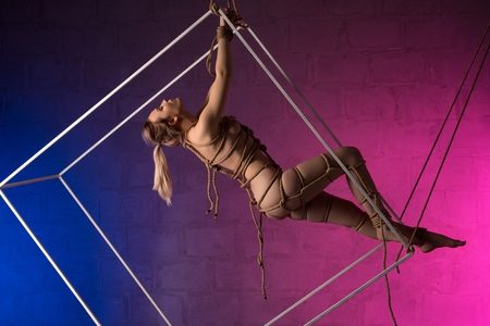 Nude girl tied up in shibari style profile shot