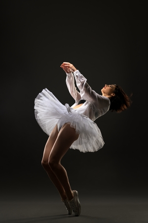 Slim brunette in ballet tutu dancing