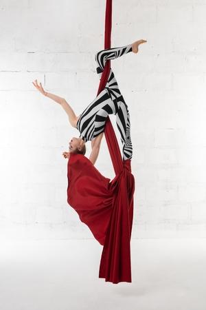 Slim girl hanging upside down on cloth view