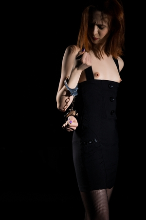 Pretty woman in handcuffs and dress shot