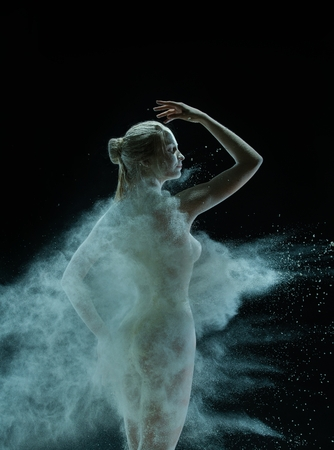 Naked girl in white dust cloud shot in the dark