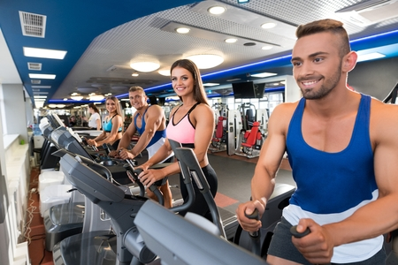 Young sporty people on simulators in a gym