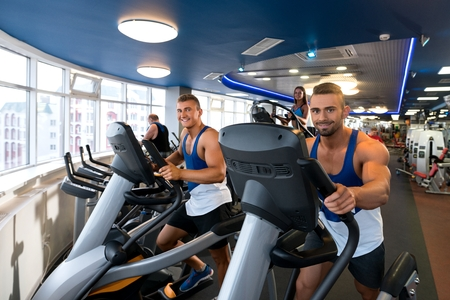 Young sporty males on simulators in a gym