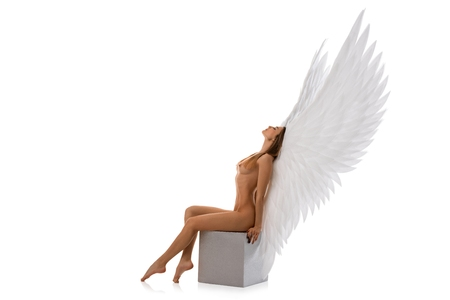 Girl in the nude with white wings on the cube
