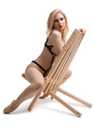 Blonde en lingerie sur une chaise isolée shot