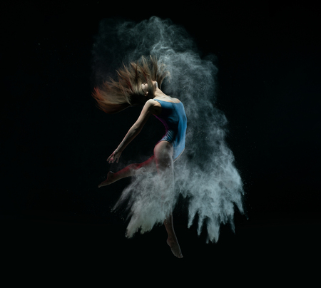 Female dancer jumping in cloud of dust