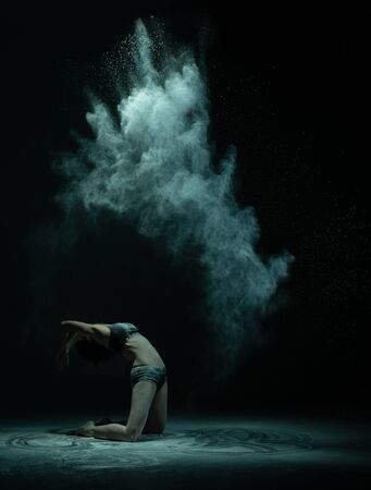 Anonymous female dancer throwing powder in air