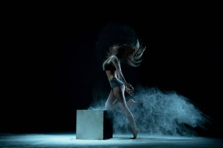 Graceful girl in white dust cloud view in the dark