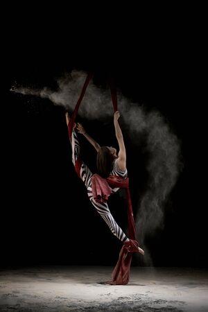 Beautiful dancer on cloth in dust cloud Фото со стока