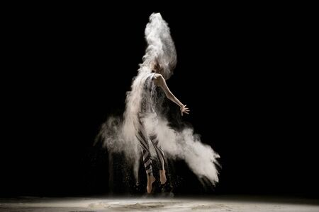 Graceful woman dancing in dust cloud in the dark