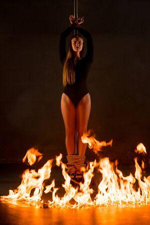Wunderschönes Mädchen mit Seil am Pylon gefesselt im Feuerschuss