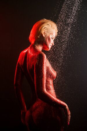 Nude blonde covered with red color in shower
