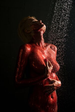 Naked girl covered with red color in shower Фото со стока