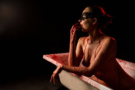 Nude woman in mask in bath with red stains Standard-Bild - 128100507