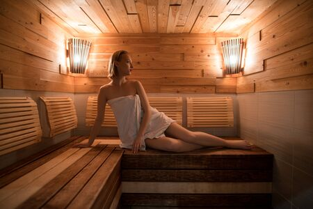 Beautiful girl wrapped in a towel in sauna