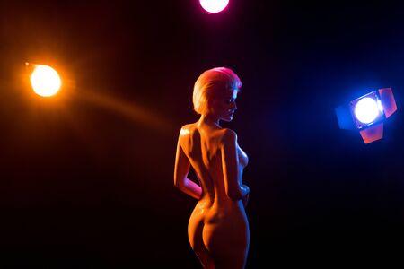 Beautiful naked woman in dark studio