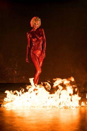 Beautiful woman in red glitter near fire