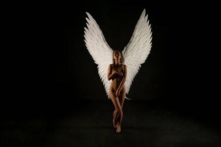 Nackte Frau mit wunderschönen Flügeln im Dunkeln geschossen