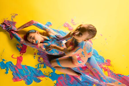 Beautiful seductive naked women covered with paint