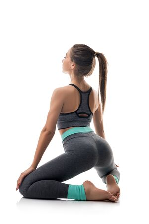 Slim girl in sportswear exercising isolated shot