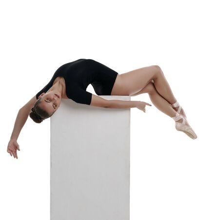Studio shot of dreaming ballerina lying on cube
