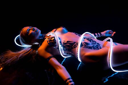 Nude woman with gold bodyart and leds shot