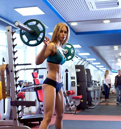 Beautiful girl posing with barbell during workout Stock Photo
