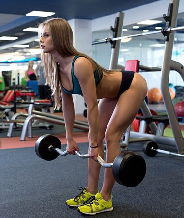 At gym. Attractive girl squats with barbell