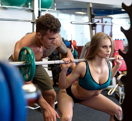At gym. Sexy coach helps girl to do squat Stock Photo - 129953017