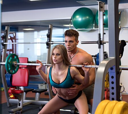 At gym. Instructor helps girl to do squat Stock Photo