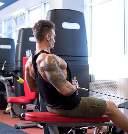 At gym. Tattooed bodybuilder trains on simulator