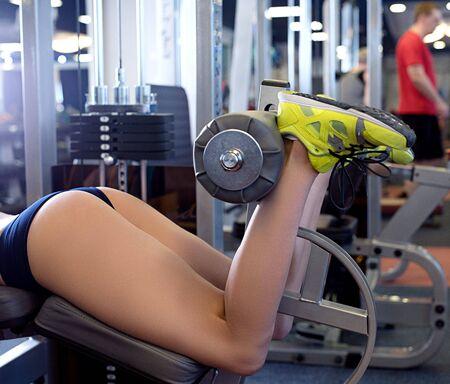 Close-up of girl exercising on simulator at gym