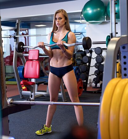 At gym. Pretty girl posing while holding barbell