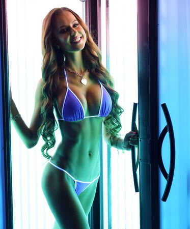 Photo of busty model posing in tanning booth