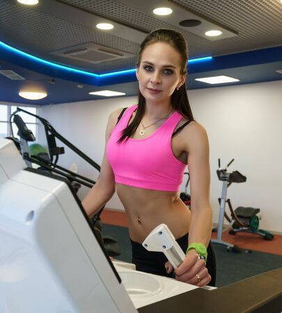 Cute young woman posing in modern fitness room