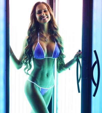 Brunette with perfect fit body posing in solarium