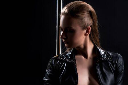 Studio shot of hot go-go dancer posing with pole Stock Photo